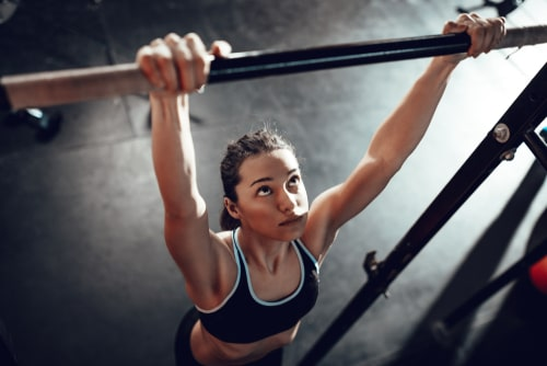 チンニングスタンドで懸垂をする女性