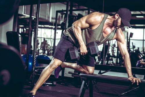 ダンベルワンハンドローイングで背筋を鍛える男性