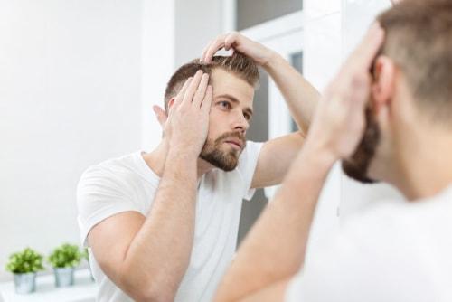 頭髪をチェックする男性