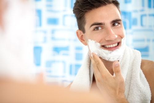 シェービングクリームを顔に塗る男性