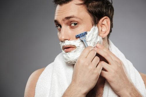 T字カミソリで髭を剃る男性