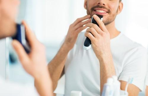 シェーバーを使って髭を剃る男性