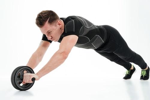 腹筋ローラーをする男性