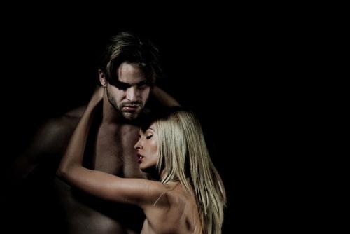 裸の男性に腕を絡める女性